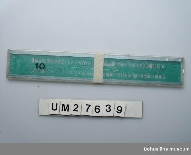"""Föremålet visas i basutställningen Uddevalla genom tiderna, Bohusläns museum, Uddevalla.  594 Landskap Bohuslän. Hålmall av grön genomskinlig plast med aluminiumkanter förvarad i ofärgat plastfodral i två delar. På hållmallen finns utstansade bokstäver, sifrror och andra symboler. Hålmallen märkt """"932/10 A. W. FABER CASTELL FEDER PEN 510 MADE IN GERMANY"""".  Ett speciellt ritstift användes ihop med hålmallen.  Föremålen UM27634 - UM27640 har använts på Uddevallavarvets ritningskontor."""
