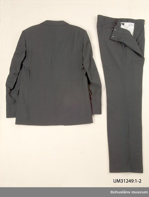 Svart kostymbyxa (UM031249:2) sammanhörande med kostymkavaj (UM031249:1).  Kostymbyxa i svart ylletyg. Ofodrade. Linning med hällor för bälte, knäpp framtill med slejf. Dubbla motveck i varje framsida. Gylf med dragkedja. Två snedställda sidfickor, en infälld bakficka med dekorknapp med tamp. Fickor av vitt bomullstyg.  På insidan etikett med uppgift om storlek, B154. På baksidan uppgifter om kvalitet (100% Ren ny ull) och tvättråd.