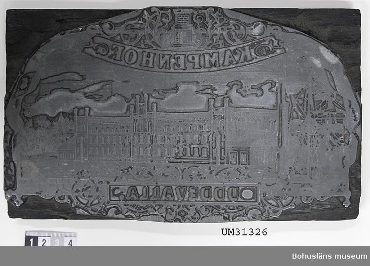 Kliché pav bly å träplatta av ek med Kampenhof AB:s logotype. Illustration: Texten KAMPENHOF UDDEVALLA  och där emellan fabriksbyggnaden.