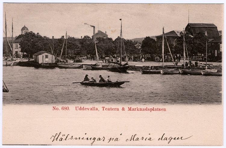 """Tryckt på kortet: No. 680. """"Uddevalla, Teatern och Marknadsplatsen."""" Skrivet på kortet: """"Hälsningar på Mariadagen."""""""