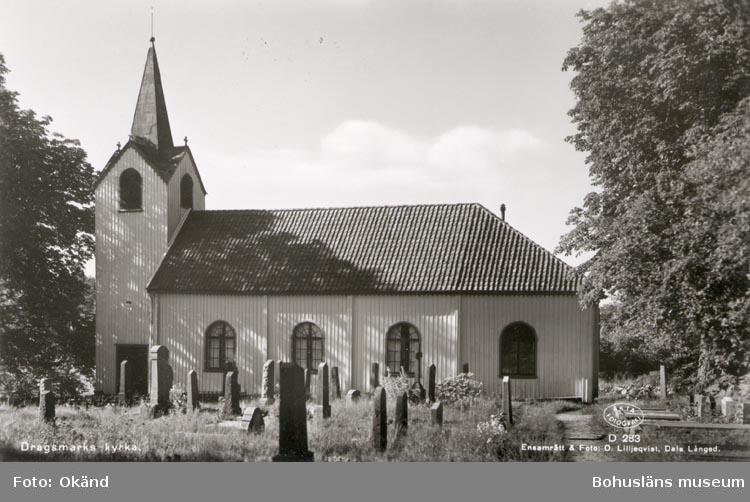 """Tryckt text på kortet: """"Dragsmark Kyrka"""". """"Ensamrätt & Foto O Lilljeqvist, Dals långed"""". """"Förlag: Firma John Hennings Efter. Dragsmark"""". Noterat på kortet: """"DRAGSMARK SN SKAFTÖ (BOKENÄSET) Kortet köpt 7.8.1954"""" """"KYRKAN, BYGGD 1755. BEVARAR DRAGSMARKS KLOSTERS SILVERKALK, GJORD PÅ 1200- T. AV NICOLAUS AV HIRFORD""""."""