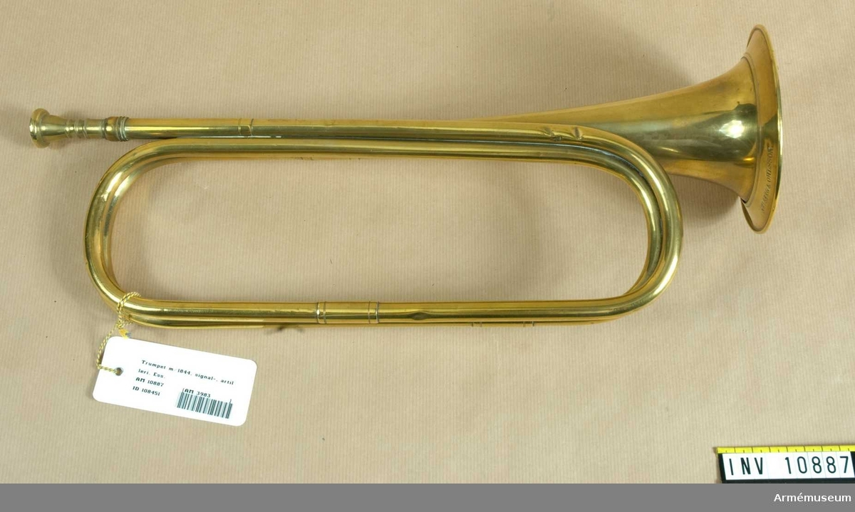 Grupp B. Naturtrumpet, signaltrumpet i Ess, av mässing i två vindlingar. Signerad på klockstycket: Ahlberg & Ohlsson (upprättstående stil). Munstycket är räfflat på skaftet. Banderoll (delvis lös) av gult och blått snöre med två tofsar. Höjd 458 mm med munstycket. Bredd 130 mm. Klockstyckets diameter 123 mm / Juli 1939. A.Lilliehöök.