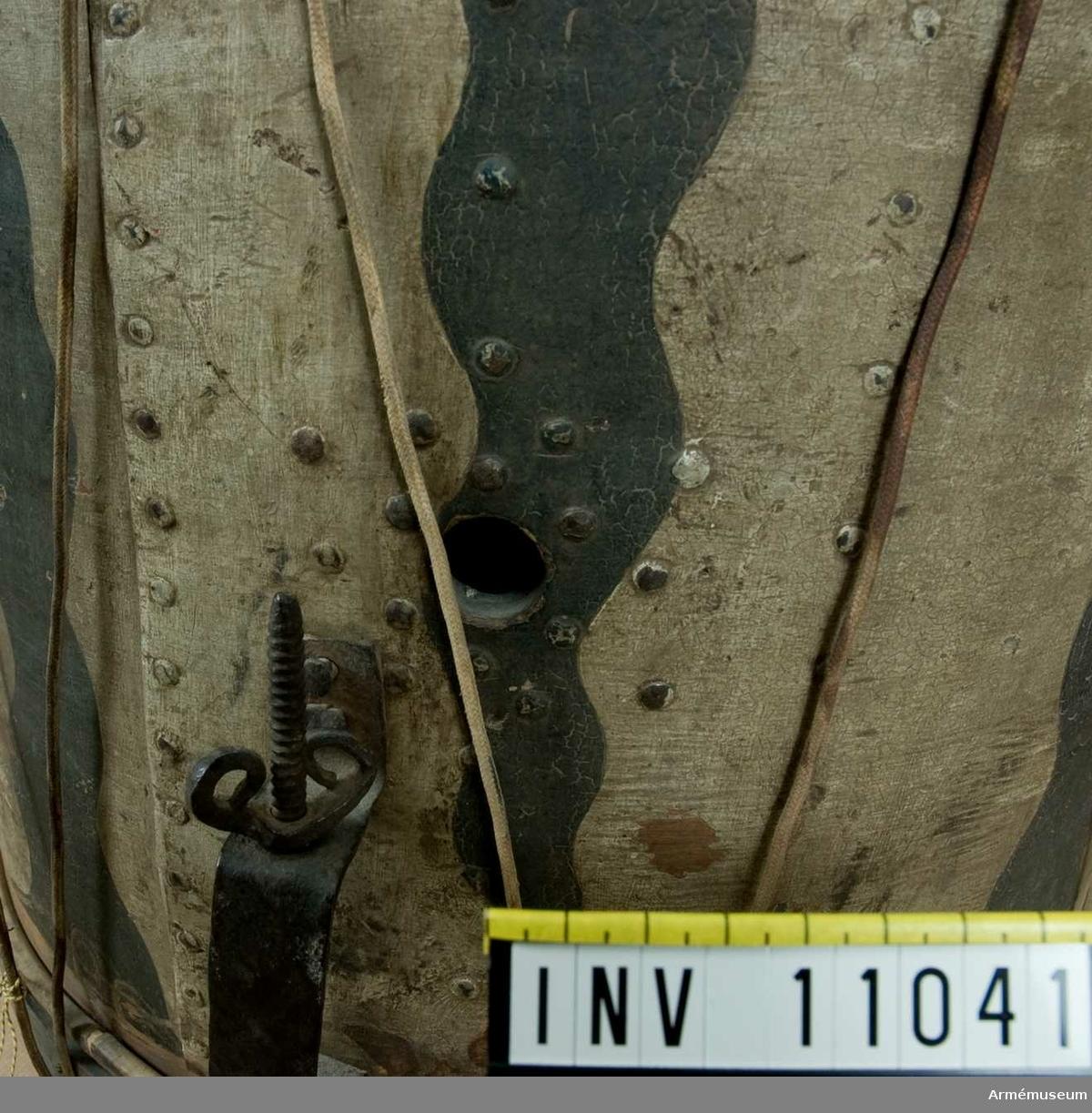 Grupp B III.  Kommer från Ryssland genom Bukowskis Konsthandel i Stockholm. Pris 500 kr. Höjd 44 cm. Diam 42,5 cm. Helt av trä.  Ramarna grön- och rödmålade. Snörad. Snarrsträngar har funnits, men saknas. Spännhållare av järn finns kvar. Väggen vitmälad och på den svenska riksvapnet (hessiska vapnet i hjärtskölden) med krönta lejon. Fältet uppfylls vidare av svarta längsgående flammor som ha en adlig krona i spetsen. Övre skinnet är borta och öppningen igensatt med en träplatta. Ramarna bör byta plats. Utställningsetikett: Trumma sannolikt använd under 1741-1743 års krig och därvid förlorad till ryssarna. Senare åter förvärvad till Sverige.