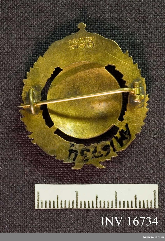 Medaljen visar det lilla riksvapnet med blå botten i emalj med  tre kronor krönt med kunglig krona med kudde av röd emalj. Omgärdat av en grönemaljerad lagerkrans på vars banderoll det står: För hem och härd. För övrigt är märket förgyllt. Förvaras i en liten platt rund svart ask.  Samhörande nr är AM.16734-16750