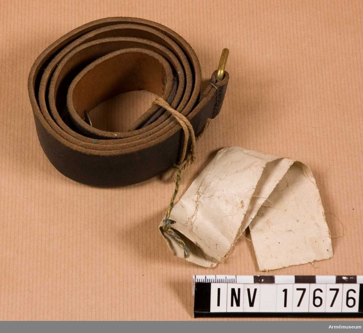 """Grupp C Gevärrem. svartfärgad, 3,5 cm bred, med spännen på ena änden och en knapp på den andra. Spänne och knapp av koppar. På remmen finns en intryckt stämpel: """"1899"""" och en stämpel med påskrift: """"29.7,1899"""" """"G.P."""" Commission de réception"""". Gevärsremmen har en pappersetikett med påskrift: """"Frankrike"""" """"Bretelle de fusil"""" """"Bekommen år 1900"""".Enligt kapten W. Granberg 1949."""