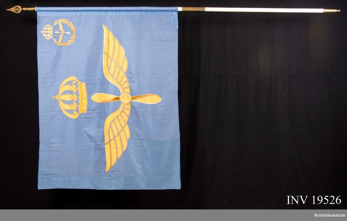 """Fana, Flygkadettskolan. Fanans motiv består av två vingar omkring en propeller krönt av en kunglig krona. I övre inre hörnet finns samma motiv inom en lagerkrans. Fanan är handbroderad. Emblem  enligt ritning från 1943 visar att  övre inre hörnet  tidigare har haft ett annat utförande, nämligen lilla riks-vapnet inom en lagerkrans. Fanan har delbar stång med följande text på doppskon: """"Flygkadettskolan"""". Fanan är konserverad 1974, 1984 och 1990, se konserveringspärm.   Samhörande nr AM 19526-19527, fana, spets."""