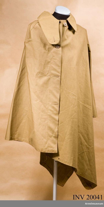 Grupp C I. Av impregnerat kakityg. Enradig med 4 benknappar på framsidan. Regnkragen kan användas som tältdel. Kragen liggande 8-10 cm bred. Den har många hål på nedre kanten (för användningen som tält).