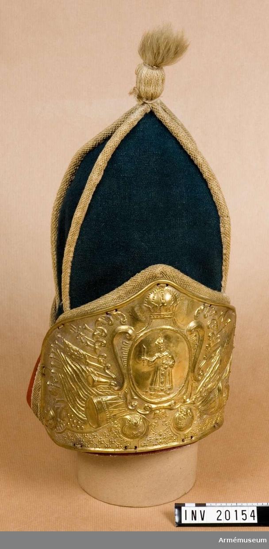 """Grupp C I. Grenadjärmössa för menig vid 1. Uglitzkj infanterireg, Ryssl. Från kejsarinnan Anna Ivanovnas regering 1730-40. Av grön, numera blått ylletyg,i fyra bitar bildande en topp med tjocka, vita garnsnören på kanten. Uppslag av rött ylle med samma snören. I mössans topp en tofs av vitt yllegarn. Mössplåt av mässing på framsidan med emblem och vapen från Anna Ivanovnas regering. I mitten staden Uglitzkjs vapen och på sidorna olika vapen, fanor och mässingsinstrument. På en fana kejsarinnan Anna Ivanovnas initialer """"A.I."""". På högra sidan ingraverade fyra ryska bokstäver, troligen namnet på fabriken och kommissariatet (enl.Wöljnskj, Hans Majestäts Kyrassiärers historia, S.Petersburg 1902, del 1, sid 126). En flammande granat av mässing  på mössans baksida. Foder av grov linnelärft. LITT  F von Stein, Geschichte des russischen Heeres, Hannover 1885, sida 105 och Knötel-Sieg, Handbuch der Uniformkunde, sida 323: År 1730 fingo grenadjärerna toppmössor med vapenplåt med respektive stadsvapen ingraverat. Mössan för infanteri- grenadjärer (armén) var grön upptill, röd nedtill, (mössan har förlorat sin ursprungliga gröna färg, som man dock kan se på sidorna och bakom vapenplåten). Wöljnskj Hans Majestäts kyrassjärers historia 1701-1901, S.Petersburg, 1902, Del 1, sida 189, 245 och Geschichte der russischen Heeres, F von Stein, Hannover 1885, sida 94, 113: Enligt dagorder 10 maj 1725 består infanterireg:a av sju fusiljärkompanier och ett grenadjärkompani. Grenadjärerna  har år 1730 till sin uniform  fått denna huvudbonad med vapenplåt. Nikolajeff. Historisk beskrivning över härskar- maktens insignier och särskilda märken inom ryska armén, S. Petersburg , Dels II, 1899, Bil. Sida 12: 38. Uglitzkjs infanteriregementes vapen; """"Furst Dimitjr i kejsarens kläder och storfurstens huvudbonad"""". (Zarewitj Dimitrj S:T Dimitrj liten pojke mördad i Ugl.)."""