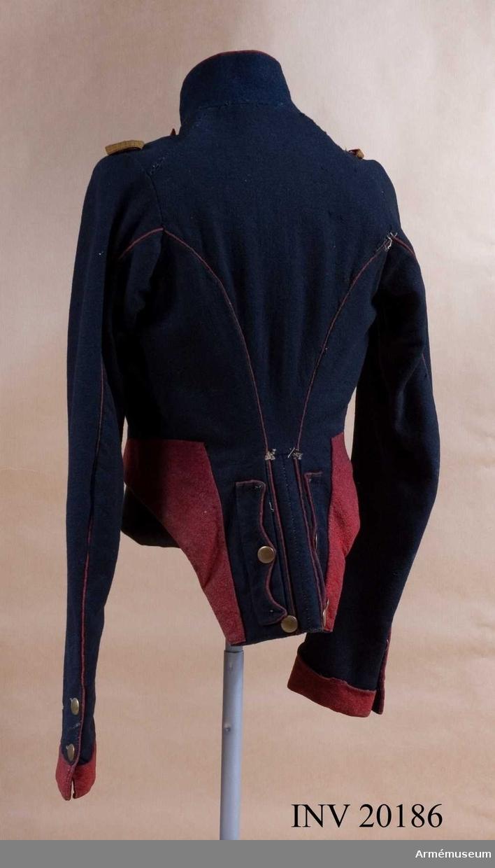 Grupp C I. Frack av mörkblått kläde med röd revär fastknäppt vid fracken med sju flata mässingknappar på varje sida. Revären sammanknäppas på bröstet med hakar. På båda axlarna ringar av gult redgarn för epåletter. På frackens nedre kant uppslag  av rött kläde. Foder av grov linnelärft. Krage av mörkblått kläde med röd passpoal på övre kanten. Fodrad med rött kläde. Tre hyskor och hakar. Passpoal av rött kläde i ärm- och ryggsöm. Skört med två fickor. Runt omkring lister av rött kläde. Runt ficklocken passpoal av rött kläde. På skörten tio flata mässingsknappar. Ärmuppslag med kavallerivinkel av rött kläde. Sprundet har två flata mässingsknappar. LITT  B Söderholm, Livgardets 2. artilleribrigads historia, sida 80: Revär med hyskor infördes i ryska armén år 1817. Armée Russe, Pajol, 1854, sida xxv: skört för ulaner och passpoal för ärm- och ryggsöm.