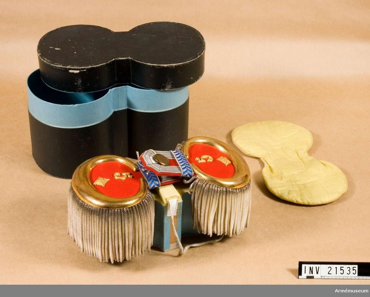 """Grupp C I. För överstelöjtnant vid 7. Bayerska infanterireg:t  """"Prinz Leopold"""". Röd klädesmatta och en guldplåt nedomkring, och på övre ändan av epåletthalsen silvergalon, b:15 mm, med tre ljusblå ränder. Fodrade med rött kläde och omkring dessa silver buljoner. På epåletterna finns stjärnor och nummer allt av guldfärgad metall. Tvärs över slejfen av blå silverbroderade band."""