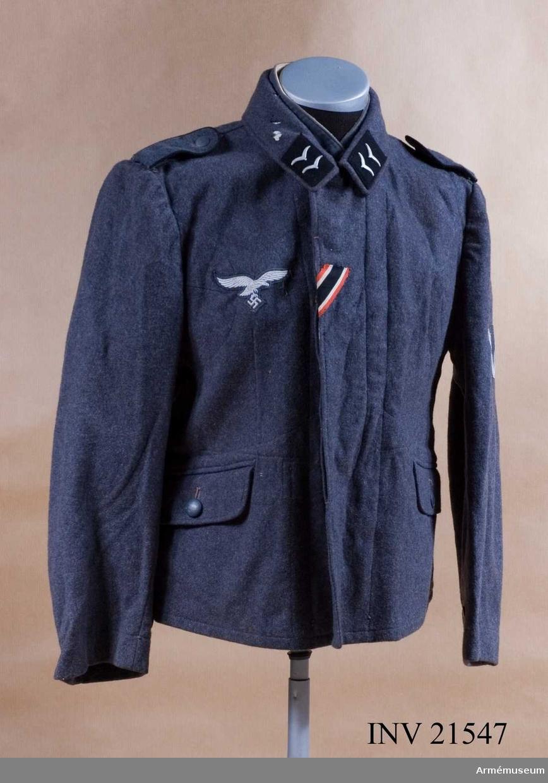 """Grupp C I. Flygarblus för Gefreiter vid Luftwaffe, Tyskland. Av fältgrå kläde. Med knäppjulp. Axelkklaffar av samma grå kläde med svart passpoil. Foder av grått bomullstyg med två innerfickor. Knappar av grå metall. Krage, öppen, nedviken med klaffar av svart kläde på kragens ända. LITT  Uniform der Deutschen Wehrmacht von Eberhard Hettler, Berlin 1939. Bilaga i färger för """"Hauptgefreiter"""" i """"Flieger- bluse"""".W Granberg."""