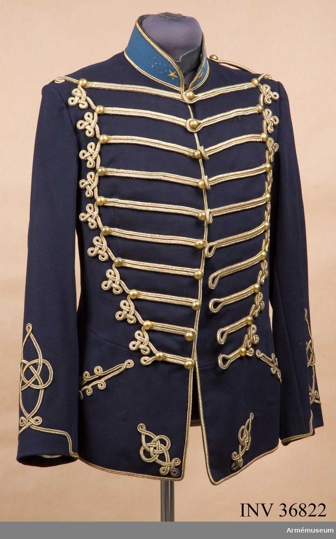 Grupp C I. Ur uniform för parad för officer vid Kungliga Skånska husar- regementet. Tillverkad mellan 1895 och 1910. Består av dolma, ridbyxor, kartusch med rem, skärp, handrem, mössa, plym, ridstövlar, sporrar, sabel, balja.