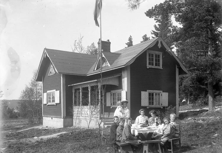 "Enligt fotografens journal nr 2 1909-1915: ""Kristinedal Telegrafstugan barnen vid m.d. bordet"". Enligt fotografens notering: ""Telegrafstugan, Fr. Anny Andersson Kristinedal Tösse""."