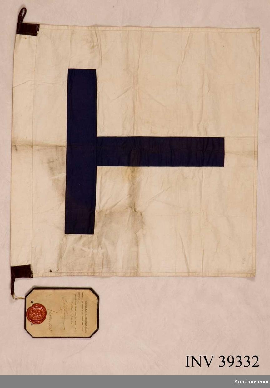 """Grupp H III.  Vit bottenduk med kanal, förstärkt i hörnen med brun läderskoning med läderöglor. På mitten ett blått """"T"""". Måttet inklusive kanal.Enl GK 1981."""