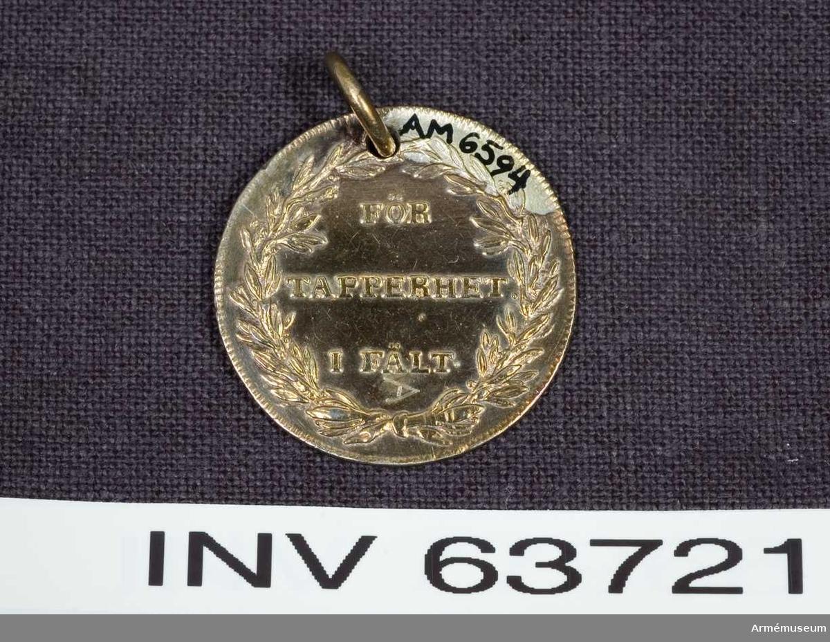 Grupp M.   Frånsidan: text på tre rader inom en lagerkrans. Medaljens kant strierad på båda sidor, randen räfflad.            Åtsidan: Text samt Bröstbild av Gustav III i bröstbild åt höger, bart huvud med långt utslaget och framkastat hår.     1789-1806.