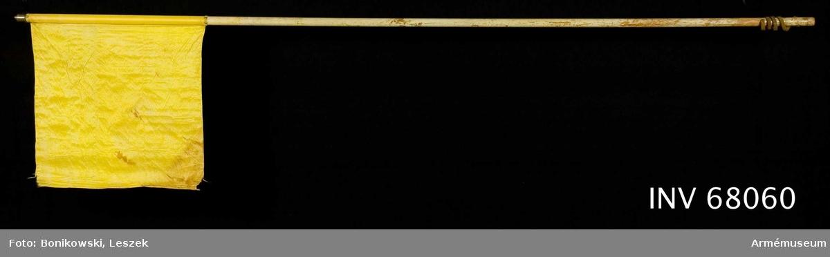 Duk: Enkel, tillverkad av citrongul sidentaft. Fållen lagd åt dukens utsida. Fäst vid stången med en rad tennlickor på ett mönstervävt gult band.  Dekor: Saknas  Stång: Tillverkad av vitmålat trä. Märken efter remhål på 675-700 mm längd, mätt från fandukens fäste.  I nedre änden ett 540 mm långt läderband, 45-65 mm från nedre änden.