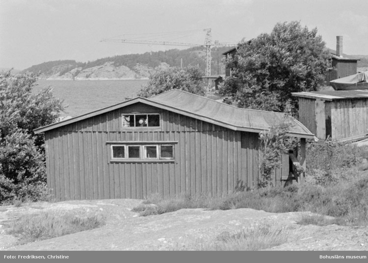"""Motivbeskrivning: """"Såtas båtvarv, Söbben. Båtbyggarverkstad uppförd av Anders och David Karlsson, Söbben (uppförd på 1960-talet). Till höger i bild, bakom verkstaden, syns ytterliggare en verkstad vilken förmodligen uppfördes på 1930-talet."""" Datum: 19800715 Riktning: Nö"""