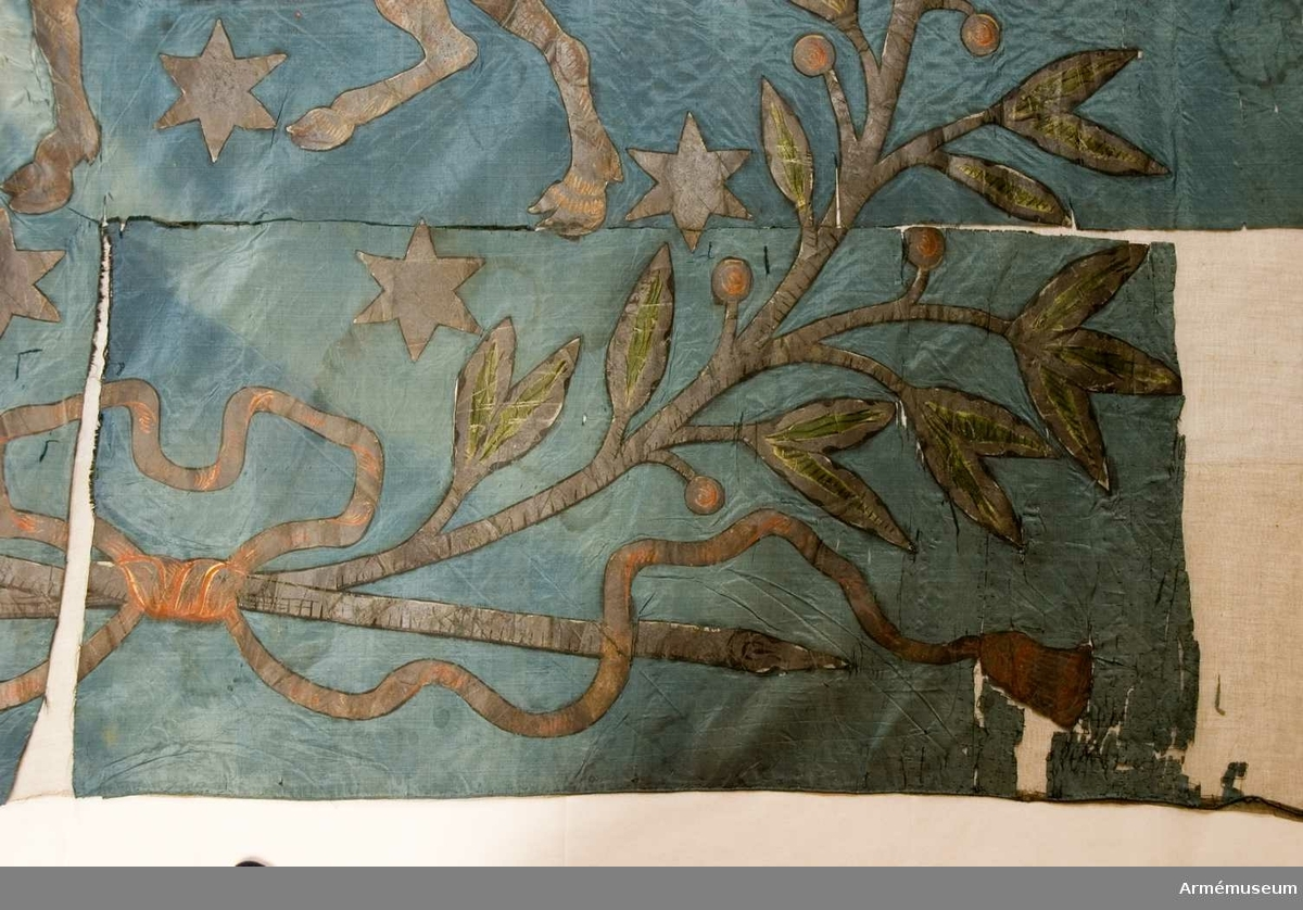 """Duk: Tillverkad av enkel blå sidentaft, sammansydd av två horisontella våder. Fäst med en rad tennlickor på ett gult sidenband. Bandet fortsätter ned, 135 mm, i spiral runt stången.  Dekor: Målad omvänt lika på båda sidor. Västerbottens sköldemärke, en ren i silver med gyllene horn och röd tunga följd av 13 stycken sexuddiga silverstjärnor, allt omgivet av en stor krans av två lagerkvistar nedtill och upptill sammanbundna, nedtill i rosett med långa tofsprydda ändar i orange. Blad i silver och grönt, bär i orange.  Dukens utsida belagd med tarlatan. I dukens nedre yttre hörn är en """"lös"""" bit rektangulär till formen (h 45 mm, b 85 mm).  Stång: Tillverkad av trä. Avsågad och förlängd med en mässingsförlängning. Mörkbrunmålad. Holk avförgylld mässing."""