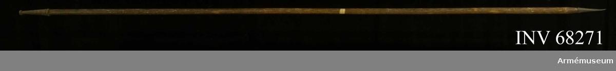 Av målad furu. Upptill en konisk spets av stål, avslutad i tillplattad knopp. Nedanför spetsen rester av bandfrans fäst med tennlikor i form av blommor. Från spetsen och nedåt cirka 30 mm förstärkning av stålskenor. Nedtill spetsig doppsko.  Märkt: vit etikett med blå rand: 1010