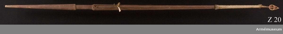 Duk av vit damast (europeisk?) med frans av vitt silke med insprängda trådar i silver, fäst vid stången med tre rader förgyllda mässingstännlikor. Duken har varit dubbel, varvid yttre sidan varit skarvad nedtill med 4 cm.   Stången kannelerad och förstärkt med järntenar ursprungligen troligen rödbemålad. Spets genombruten med krönt dubbelt C av järn, förgylld.  Av standaret återstår endast rester runt stången. Standaret är från Karl XI:s tid.