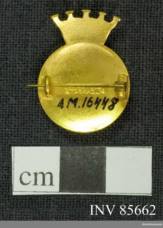 Grupp M Cirkelrund glob, krönt av en murkrona av förgyllt silver. Åtsidan: Botten av blå emalj, omgiven av en förgylld kant. I mitten ett kors av gul emalj med kanter av förgylld silver. På korsets horistontala del äro i blå emalj med förgyllda kanter infattade SLK.  Frånsidan: Utan ornering. I mitten är inpräglat WESTINS STOCKHOLM på 2 rader. Broschen är försedd med en säkerhetsnål.