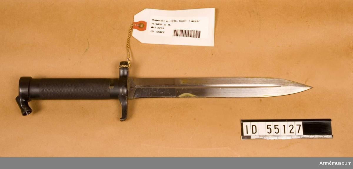 Knivbajonett m/1896 t gevär m/1896, m/1938/automatgevär m/1942. Helt tillv. av stål med rörformigt lättrat grepp med konisk låsknapp och pipring. Rak, eneggad klinga med smal blodskåra på båda sidor. Klingb vid fästet: 25 mm. Pipringens id: 15,5 mm. tillv.nr 602.