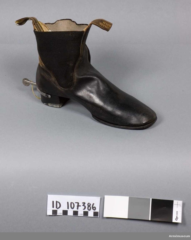 Grupp C I. Ett par Kängor av läder med resår, klack och sula. Två öglor för pådragning, en fram märkt AUG. LINDMARK STOCKHOLM, en baktill utan märkning. En träsula i kängan finns sedan den var utställd. Kängor med tvär tå. Resårkängor enligt äldre uppställning. Ur paraduniform för officer, löjtnant, vid Göta artillerireg. Fastställd modell 1845. Består av vapenrock, epåletter, byxor, kask, kängor med sporrar,skärp, kartusch med rem, sabelkoppel, portepé.