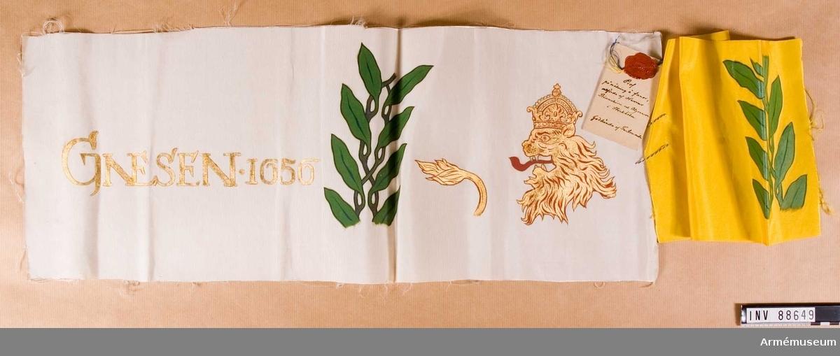 Vitt och gult siden bemålat, med vidhängande etikett med text: Prof på målning å fanor utförda af Herrar Bianchini och Algrenson i Stockholm. Godkända af Fankommittén. Bil. D N 1