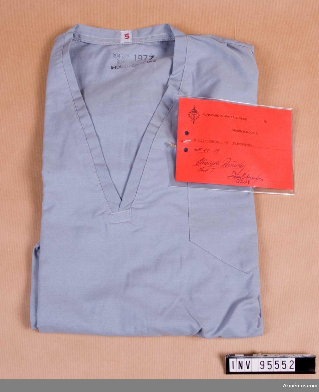 """Vidhängande etikett: """"Försvarets materielverk Originalmodell M 7325-001000-9, Pyjamasjacka, 1985-09-05 Elisabeth Rönnberg Int T / Göran Olmarker Q Int T""""."""