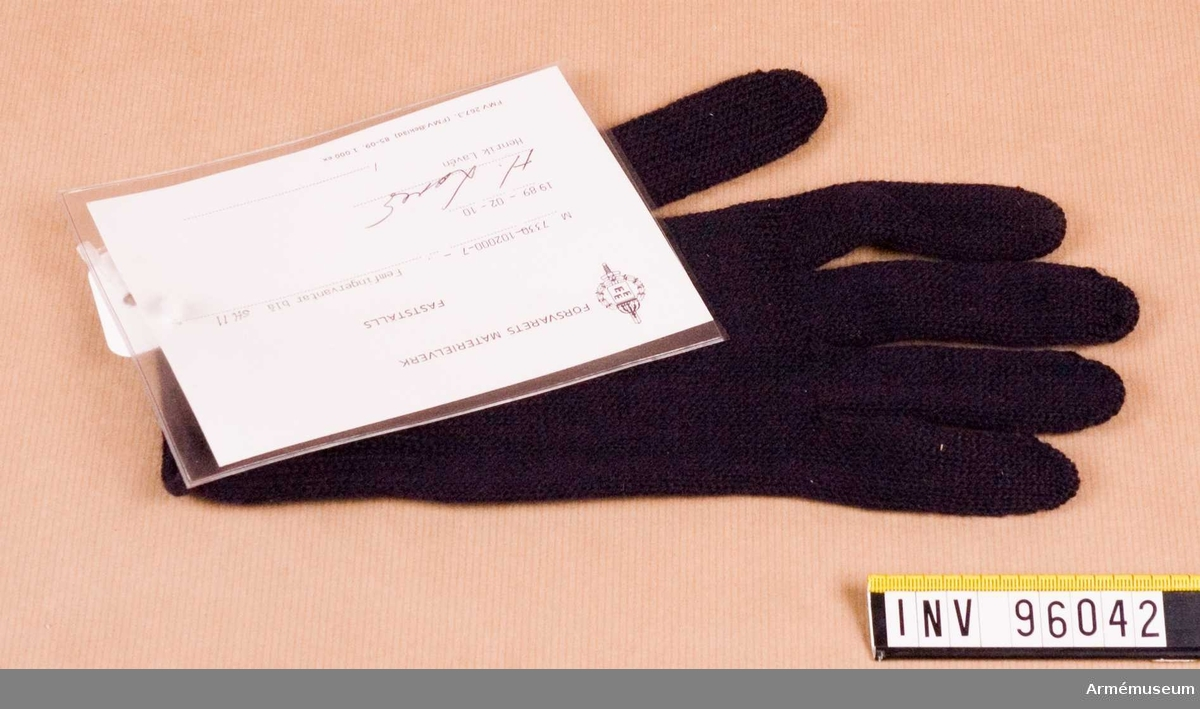 """Vidhängande etikett med text: """"Försvarets Materielverk, Fastställs, M 7330-102000-7, Femfingervantar blå, 1989-02-10, Henrik Lavén"""""""