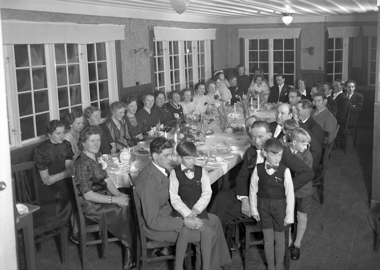 """""""Brudpar med gäster vid ett bord"""""""
