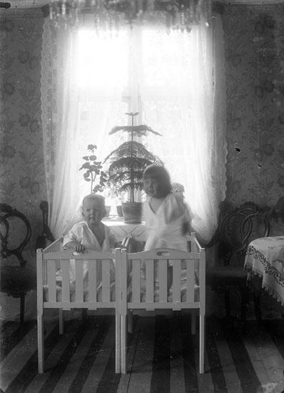 Två barn i två likadana vitmålade sängar