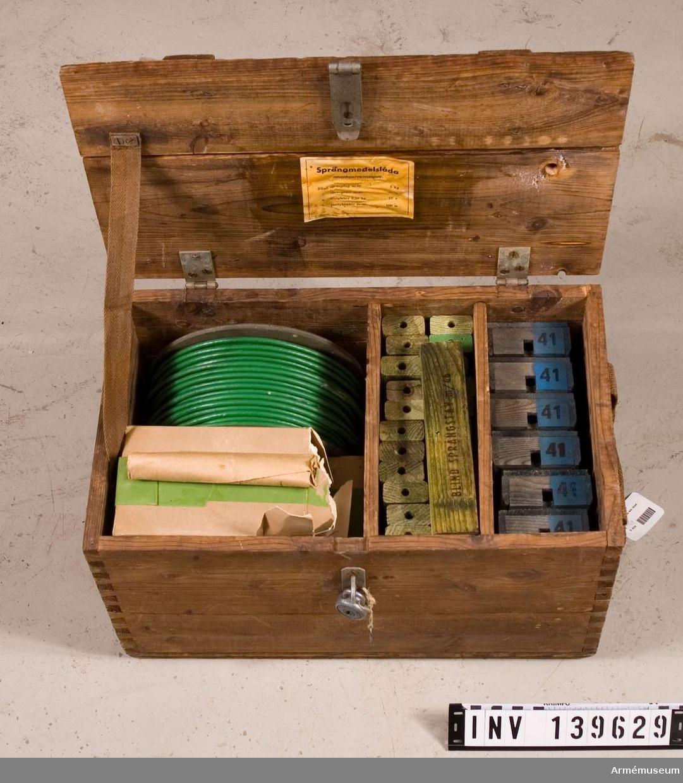Lådan innehåller: 23 st sprängstavar m/1946, blinda, av trä. 6 st övningstrampmina m/41, saknar laddning. 5 st paket á 1 kg blind sprängdeg m/1946. 1 rulle blind pentylstubin m/1947, 100 m.  Enligt etikett på lådans insida ska den innehålla: Blind sprängdeg m/1946, 5 kg, Blind sprängstav m/1946, 23 st, Blind trotylstav 0,25 kg, 23 st, Blind pentylstubin m/1947, 100 m.