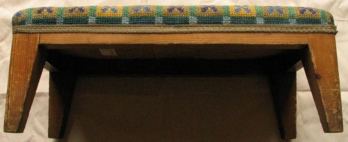 Pall. Stomme av trä, yttermått 430x210. Broderad i tvistsöm med lingarn på hardangerlinne. Enkla, blå blommor i rutor. Runt broderiet är ett handvävt band  i bomull monterat ,12mm brett.