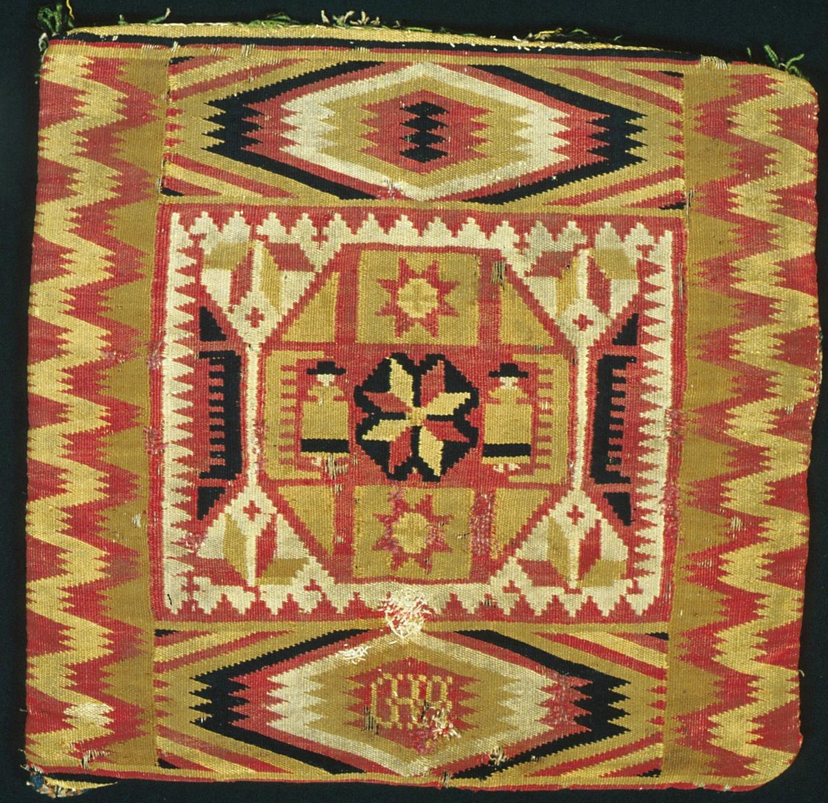 """Dyna, så kallat jynne vävt i rölakan och viggrölakan. I mitten en åttakantig ruta inneslutande en spetsuddig stjärna omgiven av två människofigurer samt två mindre spetsuddiga stjärnor. Viggbård längs långsidorna och spegelvända viggar längs kortsidorna. Blekta färger i gult, rött, brunsvart, gulgrönt och naturvitt/-ljusgrått. Invävd märkning, troligen """"MHD"""" i en av spegelviggarna.  Varp i z-tvinnat lingarn, 6 trådar/cm. Inslag i dubbelt 1-trådigt ullgarn, 10 inslag/cm. Bakstycke vävt i bunden rosengång i grönt, blått, brunt och rosa. Varp i z-tvinnat lingarn, 4 trådar /cm. Inslag i 1- och 2-trådigt ullgarn, 10 inslag/cm. Dynan är öppen i ena kortsidan."""