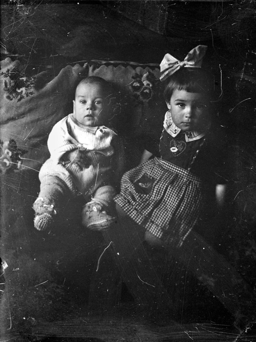 Ett spädbarn och en liten flicka sitter lutade mot en kudde.