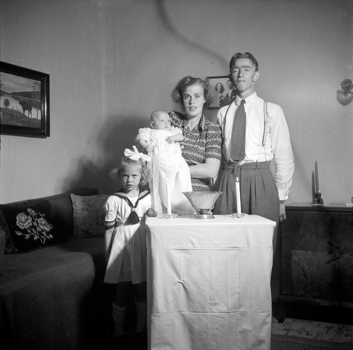 En familj i hemmet med sitt nydöpta barn.