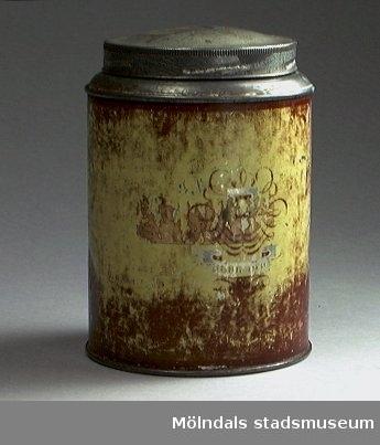 Plåtburk med skruvlock, brun/gul. Oläsligt firmamärke målat utanpå burken.