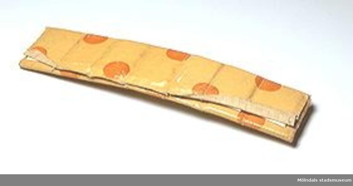 Bokstäverna skrivna på utklippta pappbitar. Förvaras i fodral med en sydd ficka för varje bokstav. Fodral av gul vaxduk med orange prickar.