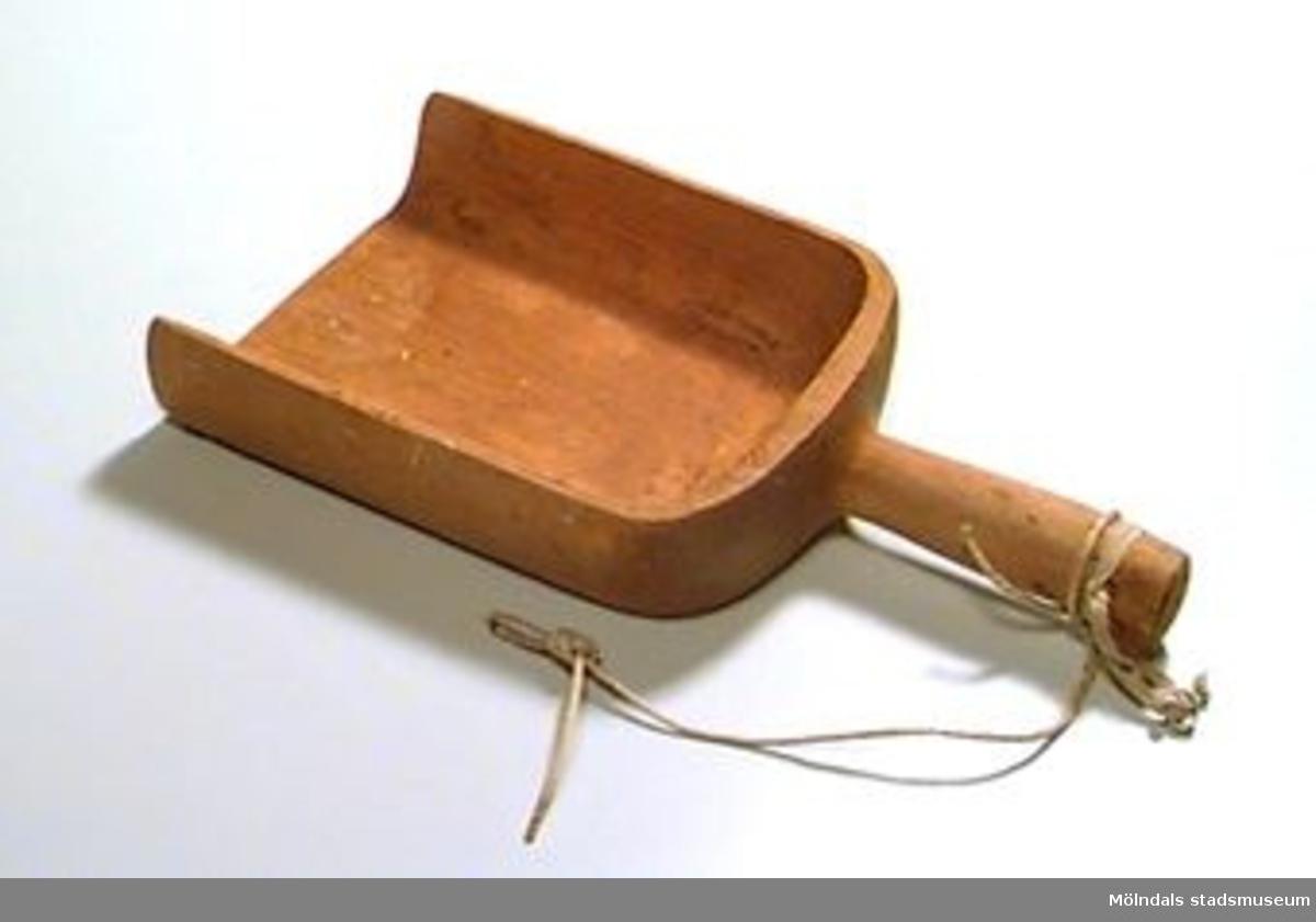 Mjölskopa skuren i ett stycke. Fyrkantig till formen. I skaftet sitter ett resårband med en ögla att hänga upp skopan i.Synliga mjölrester.Anna Andersson är givarens moster.