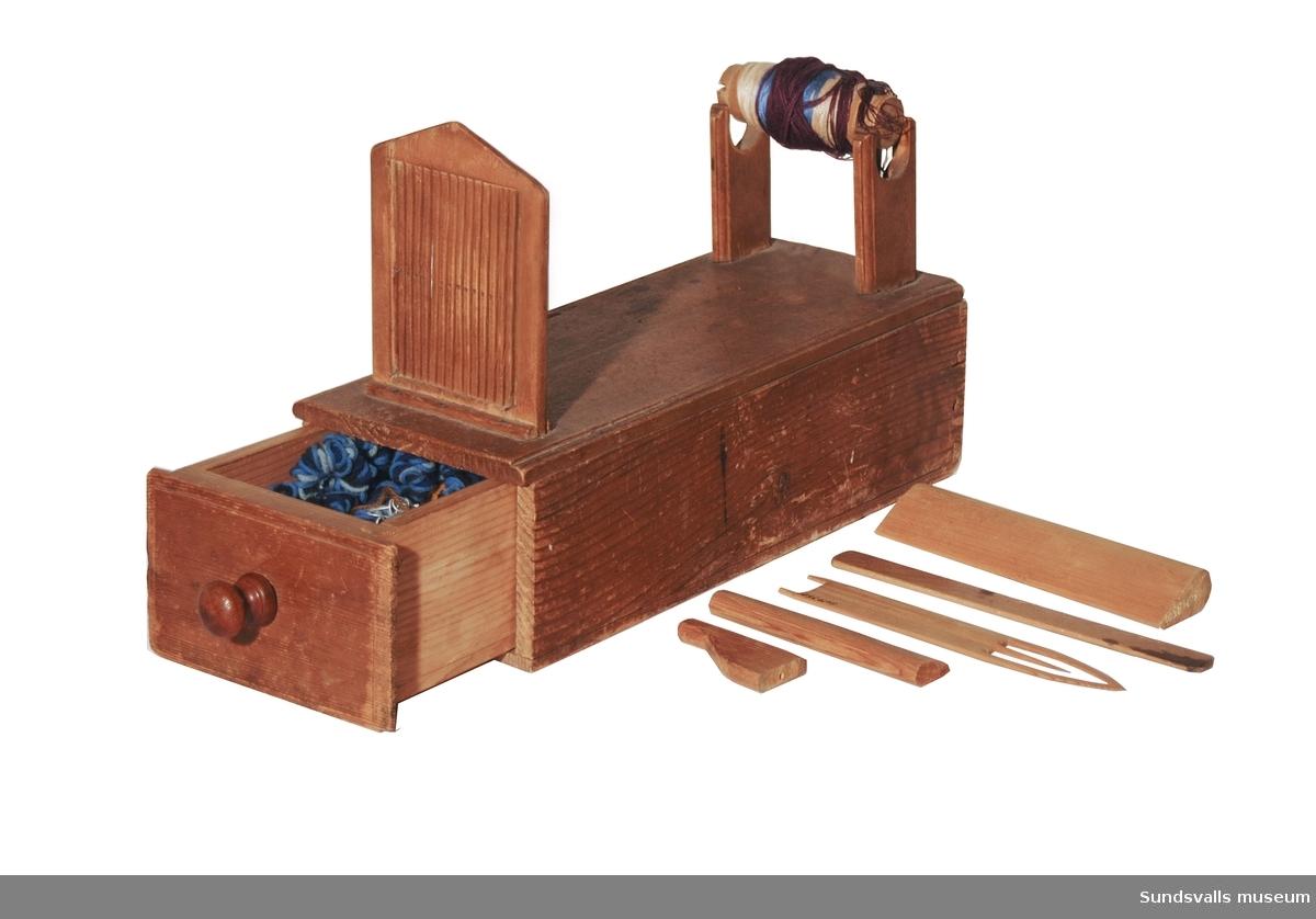 Bandvävstol, kavelfransgrind, med lådinsats innehållande vävtillbehör, samt garn och trådar. Vid vävstolens ena kortsida sitter en trärulle omlindad med garn i olika färger och en smidd spik med ett upphöjt 'S' på huvudet. Vid andra kortsidan sitter ett vävspjäll genom vilket man ska dra varpen.
