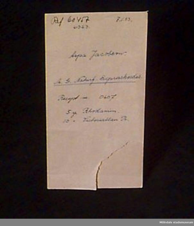 """Brunt omslagspapper, glätttat på en sida. Skrivet med bläck """" Ref. 60457, 7.1.53, 6323, Aspa Jacobsson.,h(?), G. Naturf Expresskardus, Recept nr. 0607., Rhodamin 10 gr, Victoriablau R"""".Litteratur: Papyrus 1895-1945, Minnesskrift, Esseltes Göteborgsindustrier AB, Göteborg 1945."""