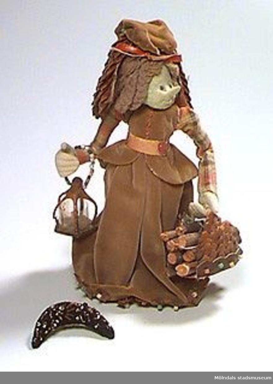 """Tygdocka med hår av grått garn och klänning i grönbrun sammet med röd-grön-gulrutiga ärmar. Ansikte och händer är gröna. Skärp av näver, skor av läder och kottefjäll. Hatt av kottefjäll, tyg och läder, samt en fjäder som dekor. I ena handen har dockan en korg med ved, och i den andra har den en lykta av trä och celluloid (?) med ett litet ljus i. Skärp, skor och hatt fastsatta med nålar. Framstycket på hatten (av svart sammet med påsydda glaspärlor) har lossnat. Färgade glaspärlor fastsydda som dekor på alla accessoarer, samt som knappar i klänningen. Papperslapp klistrad innanför kjolen: """"Får ej efterbildas"""" samt två initialer (?).Kerstin Kjellberg var föreståndare för Beda Carmérs skönhetsbutik i Göteborg. Hon gjorde dockor på fritiden tillsammans med sina kusiner, den ena handarbetslärarinna och den andra skolkökslärarinna.Givaren fick dockan av K.K. 1990."""