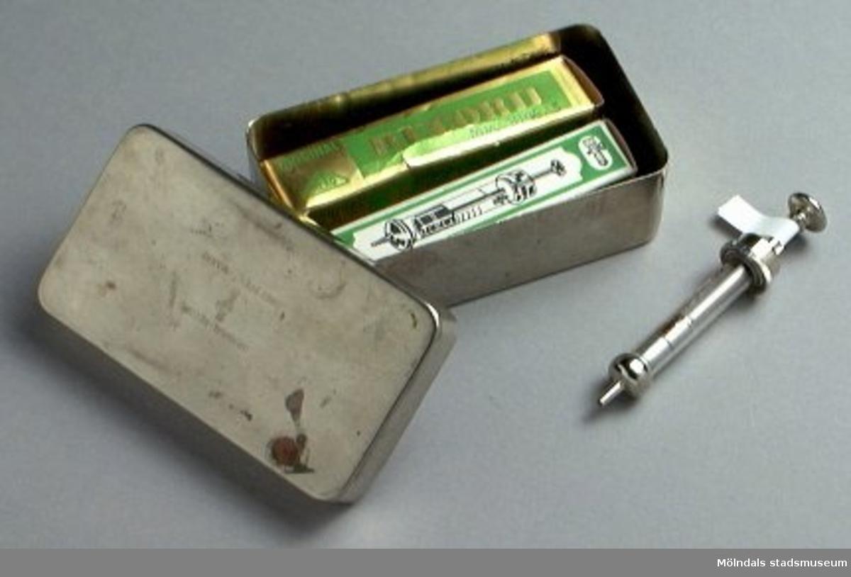 3196:1-2: Metallask, märkt Original-Record Drei Pfeil-Marke, för förvaring av injektionssprutor, lite rostig.3196:3: Original-Record pappask med injektionsspruta av glas och metall invirad i papper, 2 ccm.3196:4: Original-Record pappask med injektionsspruta av glas och metall invirad i papper, 2 ccm.3196:5: Original-Record injektionsspruta i glas och metall, ingen pappask.