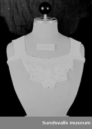 Virkad krage i vitt bomullsgarn. Virkade axelband, samt band under armhålan för att kragen ska sitta på plats. Kragen har använts av givarens svärmor, Agnes Erixon (f. 1889 i Bureå, d. 1966), maka till disponenten vid Vivstavarv, E J Erixon (f. 1889 och d. 1947).