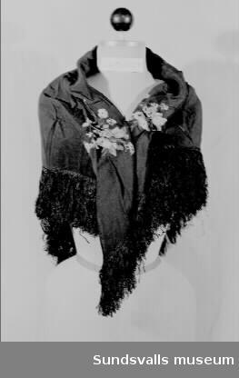 Svart schal med frans och broderat blommor. Givaren har fått schalen efter sin farmor Elsa Lena Pettersson, född 1866 i Norra Råda, Värmland, död 1942.