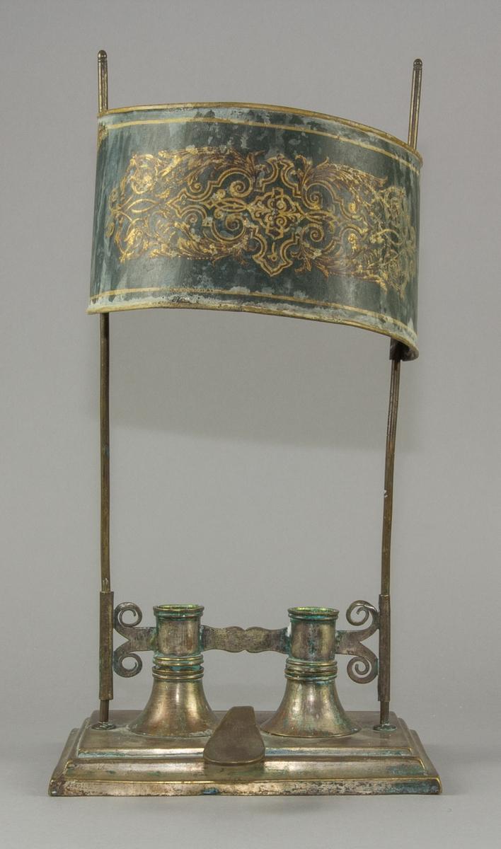 Ljusstake, bouillottelampa, handgjord av mässing: plåt, tråd och gjutna delar. Modell med rektangulär fotplatta med profilerade kanter. På denna sitter två ljuspipor, två ståndare av tråd samt ett handtag. Handtaget är gjutet (troligen) och utformat som ett tumgrepp. De två fästena för ljuspiporna är gjutna och svarvade, utformade som koner med inåtsvängda sidor, dubbla förstärkningar vid öppningarna. Ljuspiporna är förbundna med varandra av en kontursågad plåtbit, fäst genom lödning. På yttersidorna har plåten kluvits i två tungor på var sida, med utåt-inåt svängda spetsar. Dessa spetsar är lödda på hylsor, som löper på ståndarna. Ljuspiporna är raka, försedda med två förstärkningar upptill och nertill. Deras bottnar är rundade och försedda med ett litet hål. Ovanför piporna finns en skärm av mässingsplåt, halvrund, med falsade långsidor. Kortsidorna är formade till hylsor som löper på ståndarna. Skärmen är målad i grönt med ett ornament i guld. Alla delar är fästa i plattan med hjälp av skruv och mutter.