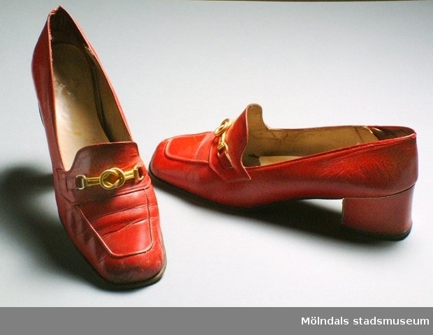 """Röd klacksko med ett guldfärgat spänne på som utsmyckning. Fabrikat eller märke går inte att se. Det är bortslitet. Man ser bara ett """"Y"""".Det finns också en tillhörande klänning: invnr. MM03344.Måtten:Längd 246 mm, bredd 68 mm, höjd 44 mm (klack)."""