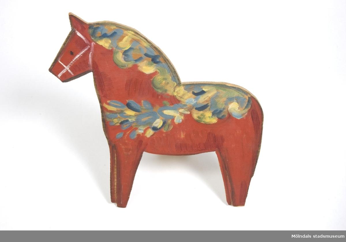 Röd dalahäst. Lövsågad och färglagd träfigur. Kommer från Bosgårdens Förskola. Tillverkad av Ingrid Hedlund(?).