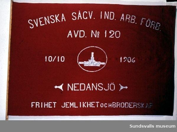 Fana i rött ylle. Texten, målad i vitt, lyder 'SVENSKA SÅGV. IND. ARB. FÖRB. AVD. No 120 10/10 1906 NEDANSJÖ FRIHET JEMLIKHET OCH BRODERSKAP'.